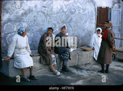 People resting on a stone bench; Bukhara, Uzbekistan. - Stock Image