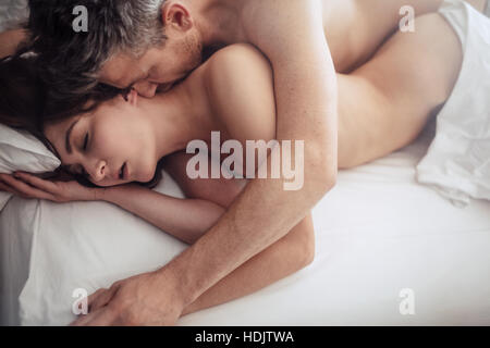 Top view of intimate lovers making love in bed. Romantic and passionate young couple on bed having sex. - Stock Image