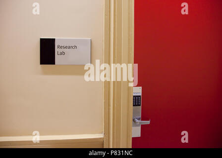 Sign on a red door with a locked keypad says the entrance to a Research Lab. - Stock Image