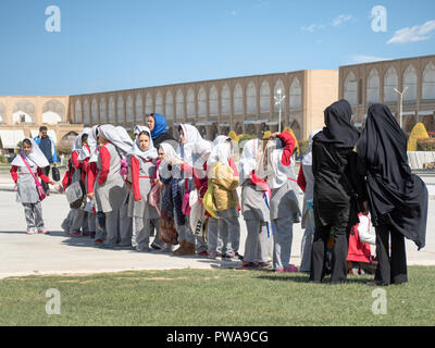 Isfahan, Iran - March 4, 2017 : primary school children with islamic veil visiting Naqsh-e Jahan square, a UNESCO famous site - Stock Image