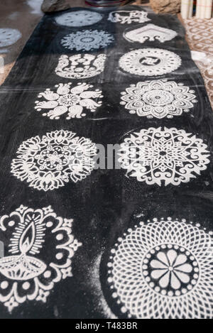 Vertical view of rangoli patterns on the roadside in India. - Stock Image