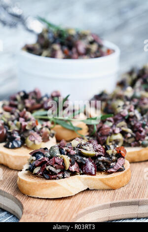 Homemade mixed Olive Tapenade made with garlic, capers, olive oil, Kalamata, black and green olives spread over toasted bread. Shallow depth of field  - Stock Image