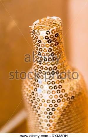 Close up of a shiny gold colored bottle in soft focus background. - Stock Image