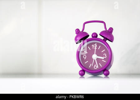 Purple alarm clock in a bright room showing the time - Stock Image