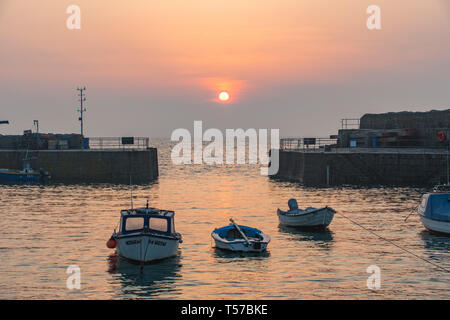 Mousehole, Cornwall, UK. 22nd Apr, 2019. UK Weather. The sun breaks through low hazy cloud at sunrise, ahead of what is forecast to be another scorching day on the coast of Cornwall. Credit: Simon Maycock/Alamy Live News - Stock Image