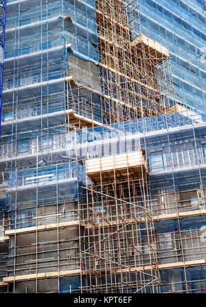 Modern business high rise apartments with exterior scaffolding because of construction works and site safety - Stock Image