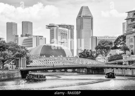 Bum boats on the Singapore river and hotels skyline - Stock Image