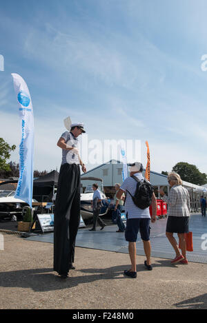 Southampton, UK. 11th September 2015. Southampton Boat Show 2015. A stilt walker with sailors t-shirt and oar greets - Stock Image