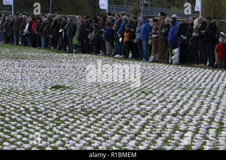 Queen Elizabeth Olympic Park, Stratford, London - 11 November  2018: People seen during the remembrance day memorial service at Elizabeth Olympic Park, London around 72,396 shrouded figures created by artist Rob Heard in memory of the fallen Commonwealth soldiers at Somme who have no known grave. The installation is made up of hand-sewing calico shrouds and bound over small figures by artist Rob Heard. Credit: David Mbiyu /Alamy Live News - Stock Image