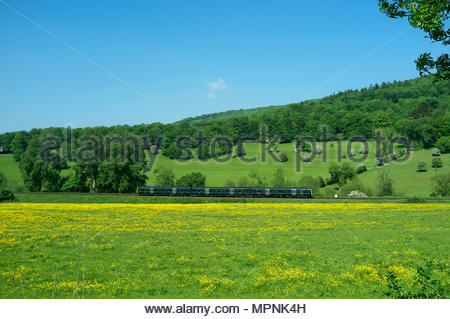 A distant view of a Great Western Railway train travelling along the Wessex Main Line near Claverton as it approaches the city of Bath, UK. - Stock Image