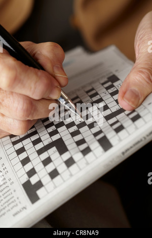 Senior woman doing crossword - Stock Image