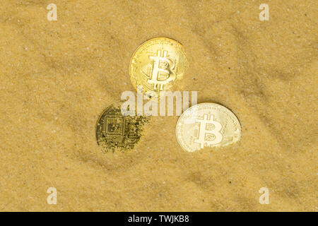 several bitcoin crypto coins on brilliant golden sand, top view. finding and mining cryptocurrency - Stock Image