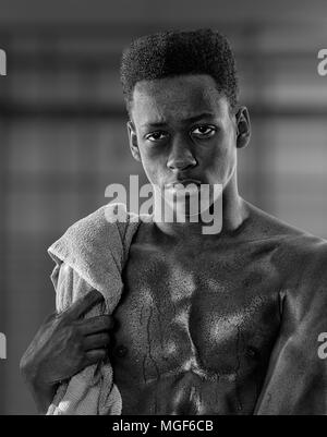 Young black man sweaty after exercise - with woel over shoulder - Stock Image