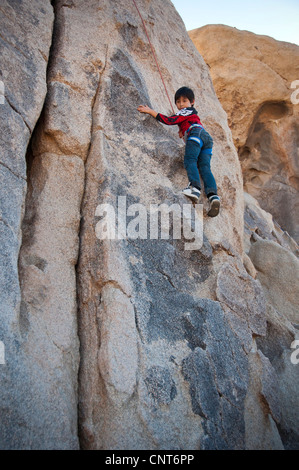 young boy rock climb climbing wall risk sport extreme outdoor nature - Stock Image