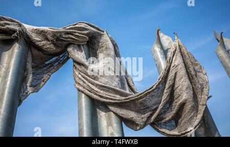 Old fabric cloth caught on metal spiked security barrier. - Stock Image
