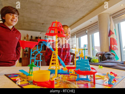 Two boys (6 and 11 yrs old) laughing together playing Mouse Trap board game - Stock Image