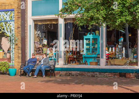 JONESBOROUGH, TN, USA-9/29/18: A man and woman rest and talk on a  bench in historic Jonesborough, in front of colorful stores. - Stock Image