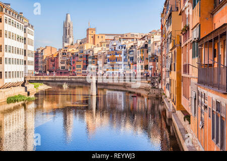 Medieval houses on the banks of the River Onyar, and the Pont de Sant Agusti, and the bell tower of Sant Feliu Collegiate Church, Girona, Catalonia, S - Stock Image