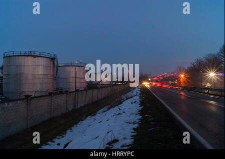 Storage tanks of a dismissed Tamoil / Amoco oil refinery plant, Cremona, Italy, night view - Stock Image