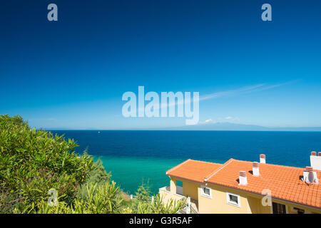 Beautiful Greek coastline with traditional house in the foreground. - Stock Image