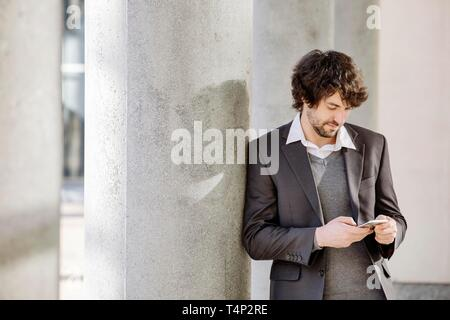 Young man leaning on column, looks on smartphone in hand, North Rhine-Westphalia, Germany - Stock Image