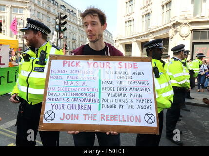 London, UK. 19th Apr, 2019. An activist seen with a placard next to police cordon during the demonstration.Environmental activists from Extinction Rebellion movement occupy London's Oxford Circus for a 5th day. Activists parked a pink boat in the middle of the busy Oxford Circus road junction blocking the streets and causing traffic chaos. Credit: Keith Mayhew/SOPA Images/ZUMA Wire/Alamy Live News - Stock Image