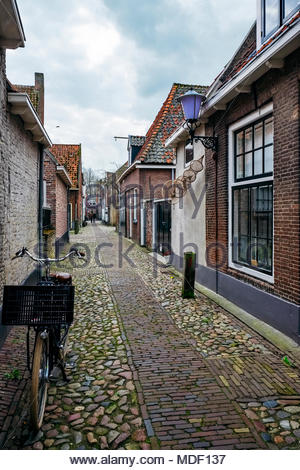 A bicycle with a basket is parked on an fietspad, or bike path, in Elburg, Netherlands; a decorative fishnet adorns a wall. - Stock Image