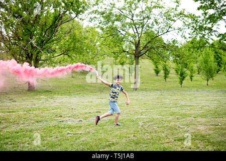 Young boy running with a pink flare trailing colorful pink smoke behind him across the grass in a park with spring trees - Stock Image