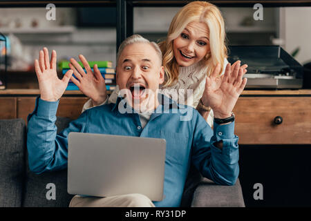 excited couple looking at laptop while having video call - Stock Image