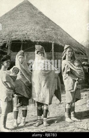 Women of the Padaung (Kayan Lahwi or Lahoi) tribe, Burma (now Myanmar), South East Asia. Two of them can be seen with brass coils round their necks. They are wrapped in blankets because of cold weather. - Stock Image