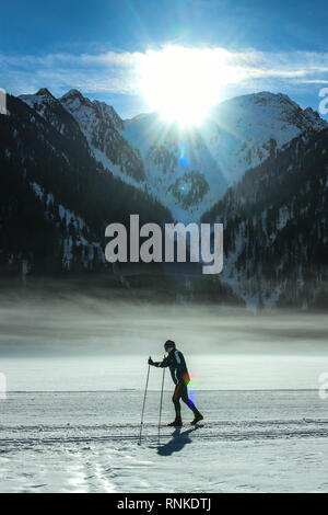 Anterselva lake, Pusteria valley, South Tyrol, Italy - February 16, 2019:  A woman skies on the Anterselva frozen lake as the early morning sun appear - Stock Image