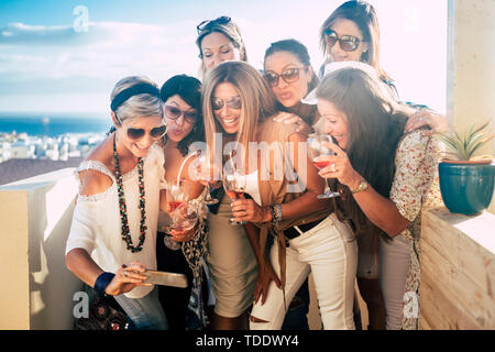Happy and cheerful people young beautiful women look a picture on a smartphone having fun - outdoor celebration concept for friends together - blue se - Stock Image
