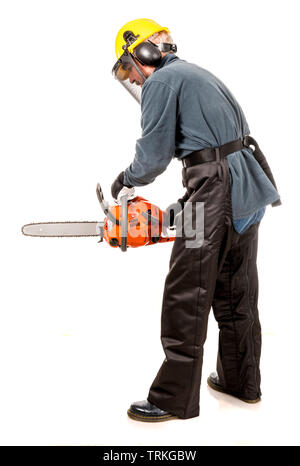 Man in safety gear demonstrating how to hold a chainsaw safely - Stock Image