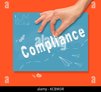 A hand picking up a Compliance concept on a colorful drawing board. - Stock Image