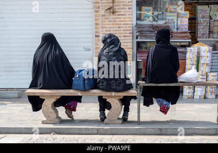 Yazd, Iran - March 7, 2017 : three women with islamic black chador sitting on benches - Stock Image