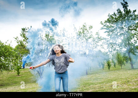 Young girl playing with a blue smoke flare running across the grass in a wooded park with a happy smile towards the camera - Stock Image