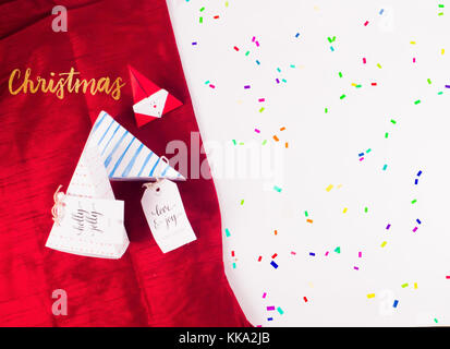 Christmas Decoration with triangle gift boxes and red scarves cloth with confetti for holidays best background image - Stock Image