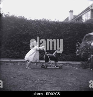 1950s, historical, infant girl in barefeet outside in a front garden pushing a toy horse on wheels, England, UK. - Stock Image