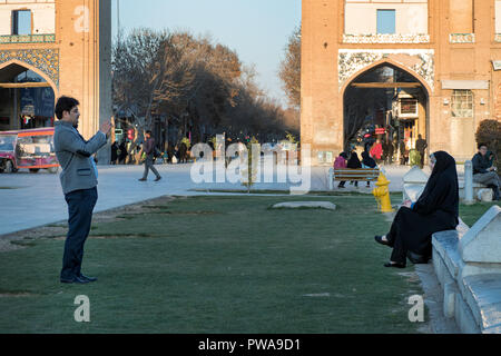 Isfahan, Iran - March 4, 2017 : young man takes a photo of his wife wearing black chador in Naqsh-e Jahan square - Stock Image