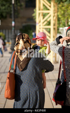 Iranian mother carrying young child whilst walking in the streer, Shiraz, Iran - Stock Image