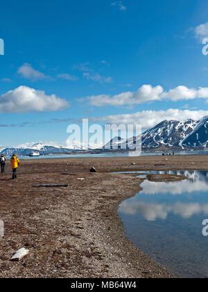 Walking along the shoreline in at Recherchéfjord Spitsbergen, Svalbard, Norway. - Stock Image