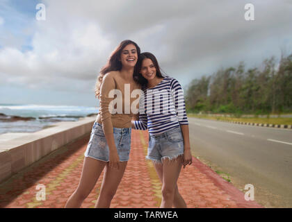 Two women standing on road beside sea holding each other - Stock Image