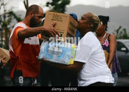 FEMA and American Red Cross volunteers distribute emergency supplies to Puerto Rican residents during relief efforts - Stock Image