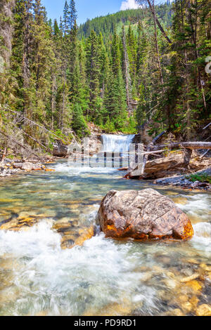 Rushing waterfall known as Stella Falls flows into Johnston Canyon creek at Banff National Park in Alberta, Canada. Johnston Canyon is a popular hikin - Stock Image
