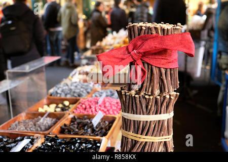 Borough Market Christmas raw liquorice sticks (licorice) Glycyrrhiza glabra with a red Christmas bow on sweets stall London England UK   KATHY DEWITT - Stock Image