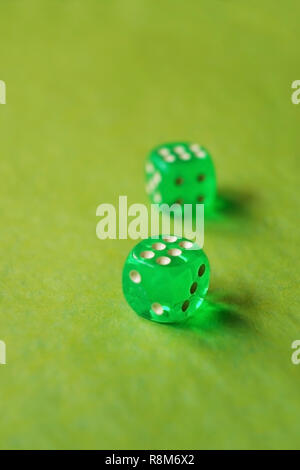 A vibrant monochromatic macro with depth of field about two green glass gambling dice with two lucky number six on green background. - Stock Image