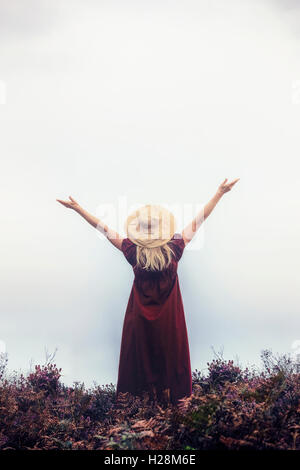 a woman in a red dress with a hat is raising her arms - Stock Image