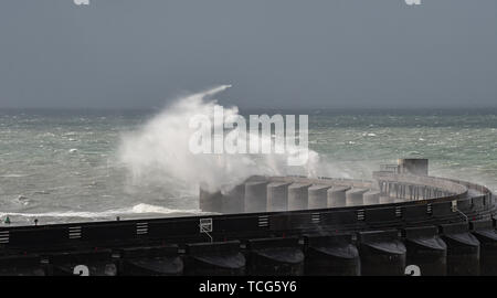 Brighton, UK. 8th June 2019.  Waves crash over Brighton Marina today as Storm Miguel passes through Britain bringing wet and windy conditions . Credit: Simon Dack / Alamy Live News - Stock Image