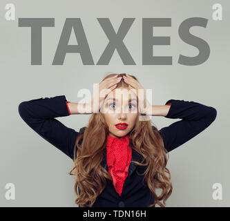 Stressed business woman with taxes inscription - Stock Image