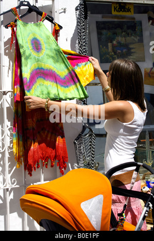 Young woman buying a colourful cotton dress from an outdoor stall Mijas Pueblo, Costa del Sol, Andalucia, Spain - Stock Image
